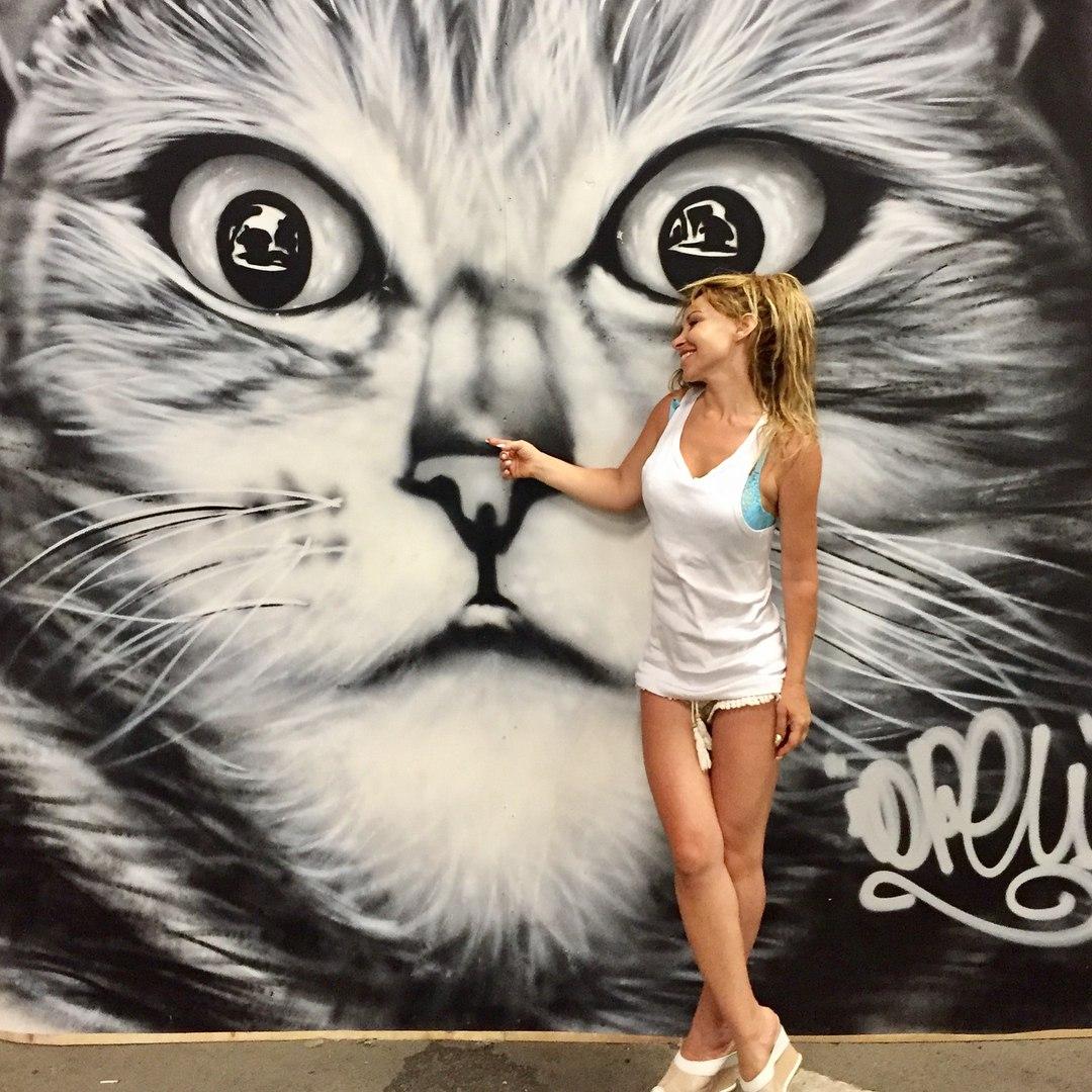 Лера Туманова в белом наряде на фоне нарисованного кота