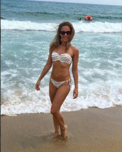 Юлия Ковальчук нам пляже в красивом купальнике в полоску