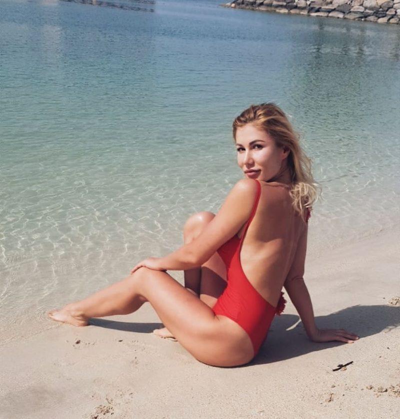 Алена Омаргалиева сидит на песчаном пляже