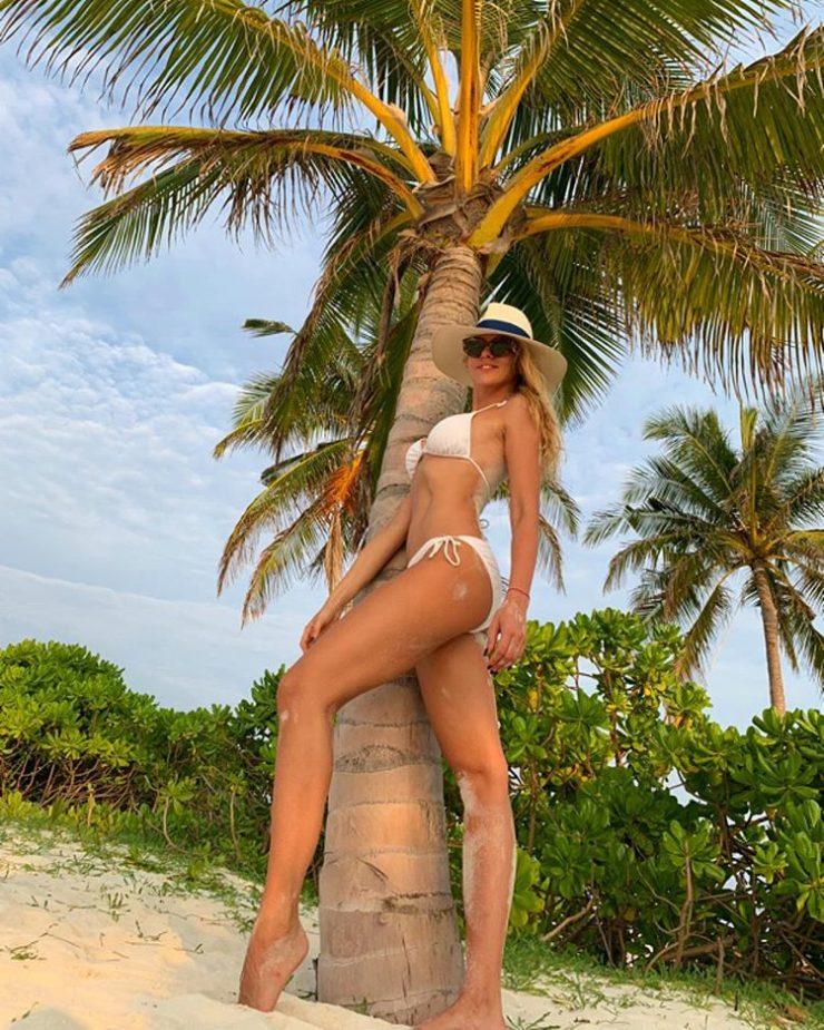 Оля Полякова позирует на фоне пальмы