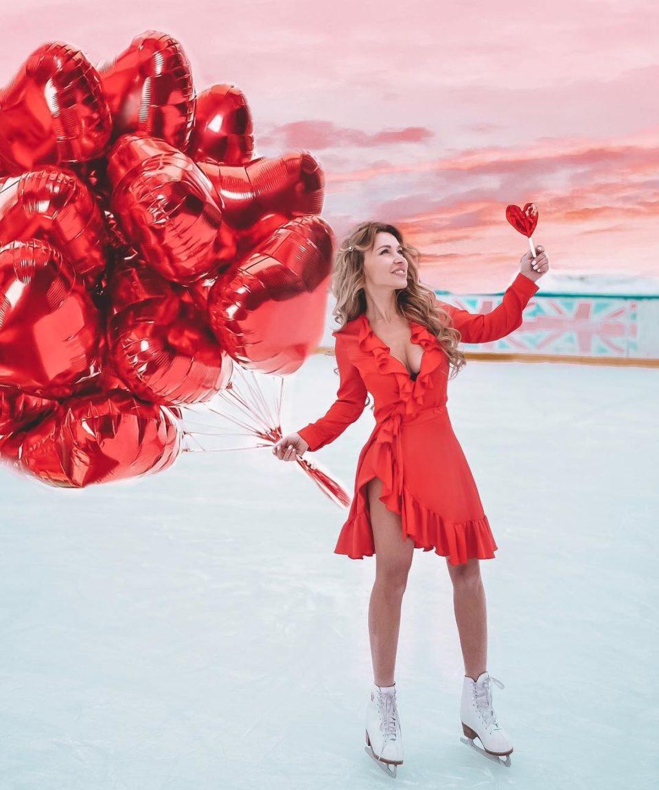 Лера Туманова катается на коньках в красном платье с воздушными шарами в руке
