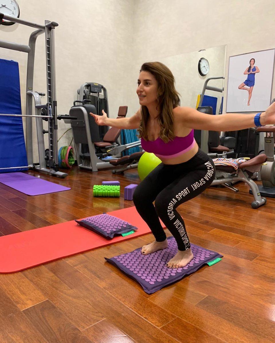 Жасмин в спортзале делает упражнения на колючем коврике