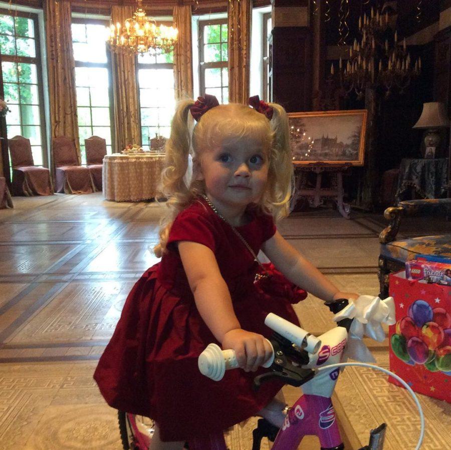 Лиза катается на велосипеде дома